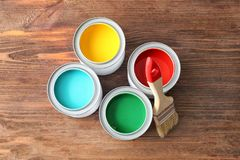 Multicolored paint in tin cans on wooden background,. Top view royalty free stock photo
