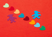 Multicolored paper boy and girl with multicolored paper hearths Stock Image
