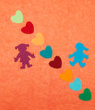 Multicolored paper boy and girl with multicolored paper hearths Stock Photos