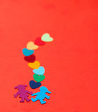 Multicolored paper boy and girl with multicolored paper hearths Royalty Free Stock Photography