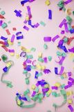 Multicolored paper confetti on a pink background. Children`s party concept stock photography