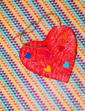 Multicolored paper hearth on a wooden red heart Stock Photos