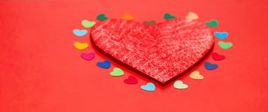 Multicolored paper hearths around a wooden red heart Royalty Free Stock Photos