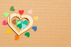 Multicolored paper hearths with a wooden  heart Royalty Free Stock Photography