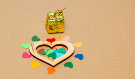Multicolored paper hearths with a wooden  heart and small present Stock Photos