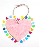 Multicolored paper hearths with a wooden pink heart Royalty Free Stock Images