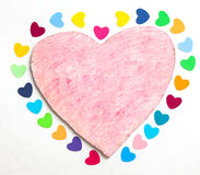 Multicolored paper hearths on a wooden pink heart Stock Photo