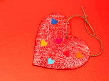 Multicolored paper hearths on a wooden red heart Stock Images