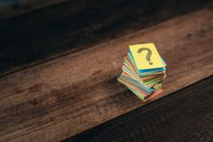 Multicolored paper with QUESTION MARK on a wooden table background stock image