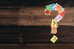 Multicolored paper with QUESTION MARK on a wooden table background Royalty Free Stock Images
