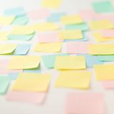 Multicolored paper stickers on wall. Photo of multicolored empty paper stickers on wall Stock Image
