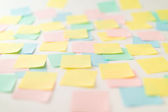 Multicolored paper stickers on wall Stock Images