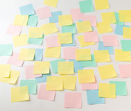 Multicolored paper stickers on wall. Photo of multicolored empty paper stickers on wall front view Stock Photo
