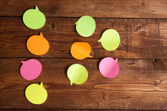 Multicolored paper stickers on wooden table Stock Photo