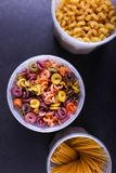 Multicolored pasta with the addition of natural vegetable dye. In a jar on a black concrete table. Top view, copy Space royalty free stock photos
