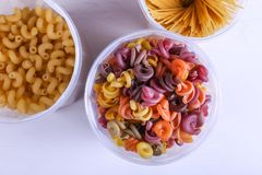 Multicolored pasta with the addition of natural vegetable dye. In a jar on a white table. Top view, copy Space stock images