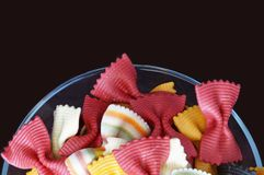 Figured pasta on a black background. Multicolored pasta. Beautiful pasta in the form of a butterfly. Original italian pasta isolated on a black background Royalty Free Stock Image