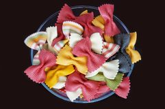 Figured pasta on a black background. Multicolored pasta. Beautiful pasta in the form of a butterfly. Original italian pasta isolated on a black background Royalty Free Stock Photo