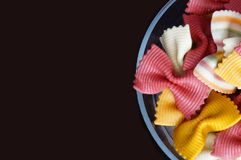 Figured pasta on a black background. Multicolored pasta. Beautiful pasta in the form of a butterfly. Original italian pasta isolated on a black background Stock Photos