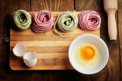 Multicolored pasta, egg yolk and daugh roller on wooden table Royalty Free Stock Photos