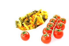 Multicolored pasta one tomato and tomato bunch Royalty Free Stock Photos