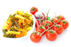 Multicolored pasta, pepper, tomato bunch and garlic Stock Photos