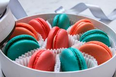 Multi-colored delicious homemade macarons in a round white box on a marble background stock photos