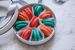 Multi-colored delicious homemade macarons in a round white box on a marble background royalty free stock photo