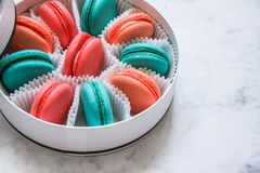Multi-colored delicious homemade macarons in a round white box on a marble background royalty free stock photography