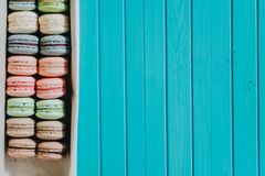 Multicolored pastel colors macaroons or almond cookies lie in a box on a turquoise background, copy space.  Stock Image