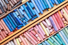 Multicolored pastel crayons in wooden artist box closeup Royalty Free Stock Photos