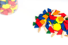Multicolored pattern blocks on a white wooden background.Box with colored cubes.Isolate. Blocks; math; children; preschool; curriculum; building; montessori Stock Image