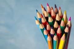 Multicolored pencils against light blue background. Closeup royalty free stock photography