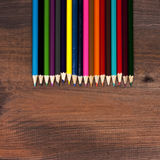 Multicolored pencils on a background of dark wood tables Royalty Free Stock Photos