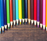 Multicolored pencils on a background of dark wood tables Royalty Free Stock Photo