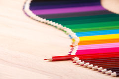Multicolored pencils on beige wooden table. Waveform border from colour pencils. Copy space. Place for text. One red pencil stand out from other pencils Stock Photos