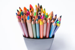 Multicolored pencils in the black box on a white background. Back to school concept. Stock Photos