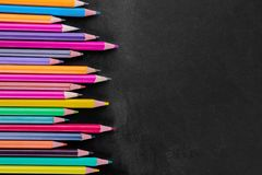 Multicolored pencils on a black school board with a place for an inscription. stock photo