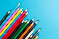 Multicolored pencils on a blue background, children`s creativity.  stock photos