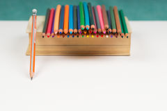 Multicolored pencils on the book. Back to school. Copy space. Top view stock photography