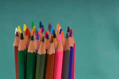 Multicolored pencils in the box on a blue background. Back to school. Copy space. Top view Stock Images