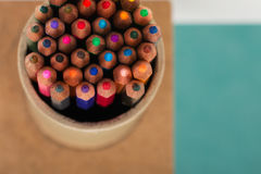 Multicolored pencils in the box on a blue background. Back to school. Copy space. Top view Royalty Free Stock Photo
