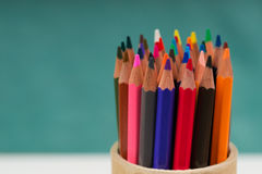 Multicolored pencils in the box on a blue background. Back to school. Copy space. Top view Stock Photos