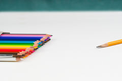 Multicolored pencils in the box on the white paper. Back to school. Copy space. Top view Stock Image