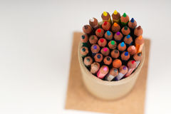 Multicolored pencils in the box on the white paper. Back to school. Copy space. Top view Stock Photos
