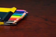 Multicolored pencils in the box on a wooden table. Back to school. Copy space royalty free stock images