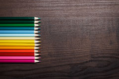 Multicolored pencils over brown table background Stock Photo