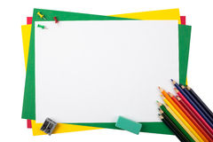 Multicolored pencils on a frame from colored paper. Multicolored pencils, push pins, an eraser and a sharpener on a frame from sheets of colored paper isolated Royalty Free Stock Photos