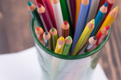 Multicolored pencils in a glass on wooden background Stock Images