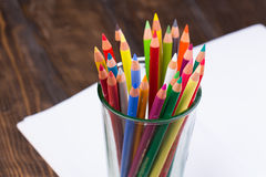 Multicolored pencils in a glass on wooden background Stock Photo
